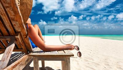 Plakat Woman at beach holding sunglasses