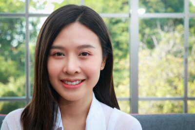 Plakat Woman beautiful white skin long hair asian Have a beautiful smile, look healthy. Sit on the sofa in the living room at home. The concept of health care for women in their 30s.