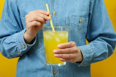 Plakat Woman hold glass of soda on yellow background