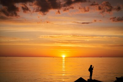 Plakat Woman or man standing on rock looking straight. Nature and beauty concept. Orange sundown. Girl silhuette at sunset.