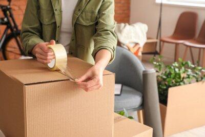 Plakat Woman packing moving box at home