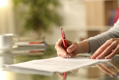 Plakat Woman signing document with pen on a desk at home
