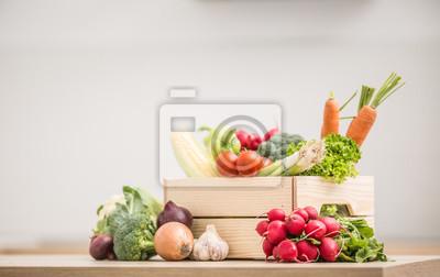 Plakat Wooden box full of fresh healthy vegetables. Broccoli carrot radish onion garlic corn on wooden kitchen table