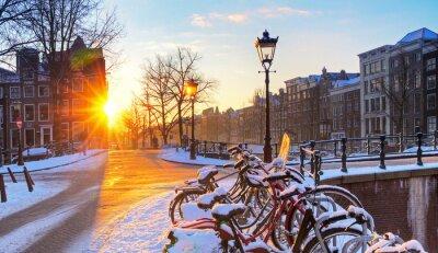 Plakat Wschód słońca nad ulicach Amsterdamu w Holandii, z rowerami pokryte śniegiem na piękny zimowy dzień. HDR