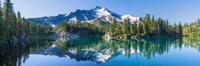Plakat Wulkaniczna góra w porannym świetle odbicie w spokojnych wodach jeziora.