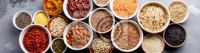 Plakat Wybór pożywienia i płatków w miskach: komosa ryżowa, chia, jagoda goji, fasola mung, kasza gryczana, fasola, kurkuma, polba, bulgur, soczewica, sezam, siemię lniane, dziki ryż, migdał na szarym betono
