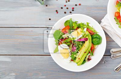 Wyśmienita i lekka sałatka z pomidorów, jajek i mieszanki liści sałaty. Zdrowe śniadanie. Widok z góry