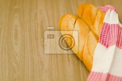 Свежий горячий хлеб, обернутый в вафельное цветное полотенце