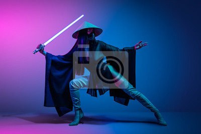 Plakat Concept on cosmic cosplay. Сontemporary portrait a young athletic woman in traditional Japanese black kimono, an Asian hat and highboots is holding a lightsaber and posing on neon blue-pink background