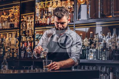 Plakat Stylowy brutalny barman w koszuli i fartuchu sprawia, że koktajl w tle kontuaru bar.