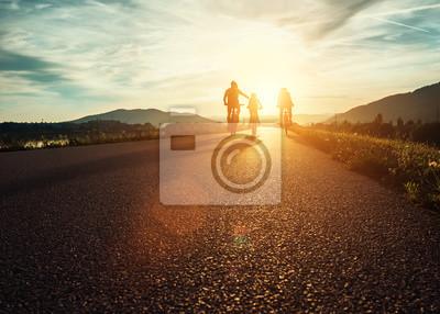 Plakat Ð¡yclists rodziny poruszający się po drogach na zachodzie słońca