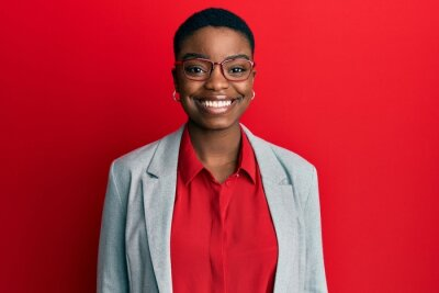 Plakat Young african american woman wearing business jacket and glasses with a happy and cool smile on face. lucky person.