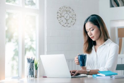 Plakat Young attractive asian woman holding mug and working on laptop at home, work from home concept.