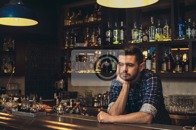 Plakat Young bartender leaning on bar counter thoughtful