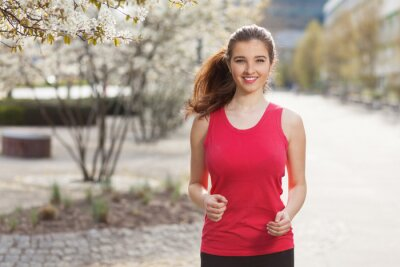 Plakat Young beautiful woman running in the city