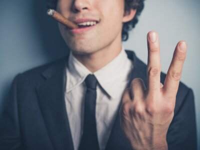 Plakat Young businessman with cigar showing rude gesture