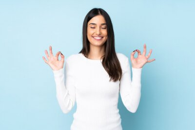 Plakat Young caucasian woman isolated on blue background in zen pose