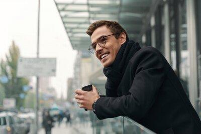 Plakat Young european businessman looking on modern city