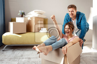 Plakat Young family couple bought or rented their first small apartment. Cheerful woman scream sitting in box. Guy move her. They play game during moving in.