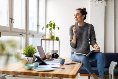 Plakat Young female freelancer working in loft office
