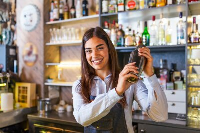 Plakat Young female worker at bartender desk in restaurant bar preparing coctail with shaker. beautiful young woman behind bar making coctail