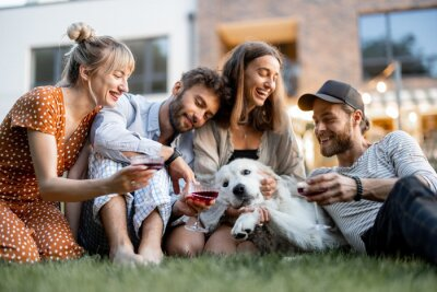 Plakat Young friends having fun playing with a dog and drinking wine, sitting on the green lawn at backyard of the country house in the evening