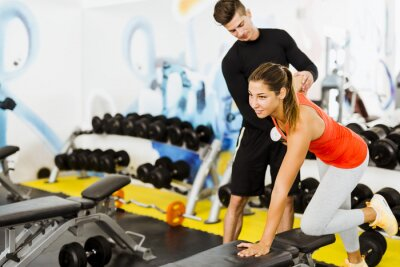 Plakat Young male trainer giving instructions to a woman in a gym