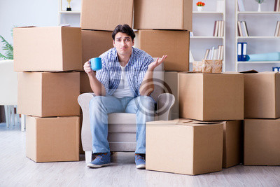 Plakat Young man moving in to new house with boxes