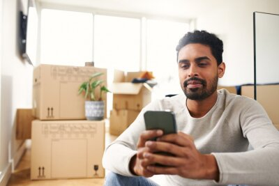 Plakat Young Man With Mobile Phone In Lounge Of New Home On Moving Day Surrounded By Removal Boxes