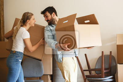 Plakat Young married couple moving into new home.They unpacking and cleaning .