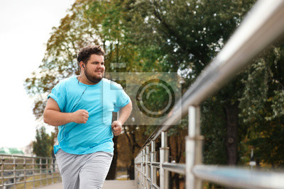 Plakat Young overweight man running outdoors. Fitness lifestyle