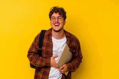 Plakat Young student caucasian man holding a laptop isolated on yellow background laughing and having fun.