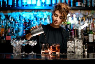 Plakat Young woman barman preparing cocktail and pouring it into glass.
