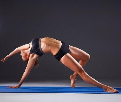 Plakat Young woman doing yoga exercise on mat