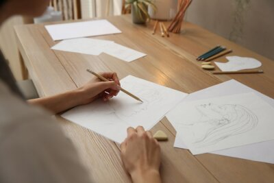 Plakat Young woman drawing male portrait at table indoors, closeup