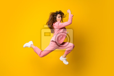 Plakat Young woman jumping over isolated yellow wall