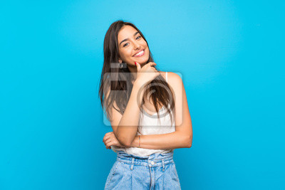 Plakat Young woman over isolated blue background smiling