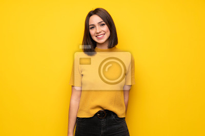Plakat Young woman over yellow wall smiling