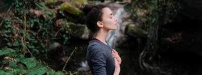 Plakat Young woman practicing breathing yoga pranayama outdoors in moss forest on background of waterfall. Unity with nature concept.