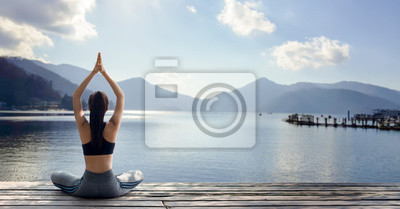 Plakat Young woman practicing yoga in the nature