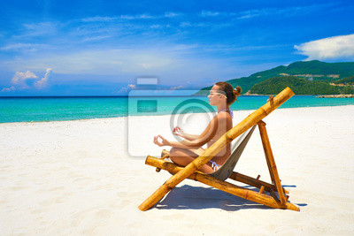 Young woman relaxing in pose yoga on a beautiful beach.