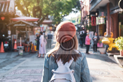 Plakat Young woman traveler walking in the shopping street, Travel lifestyle concept