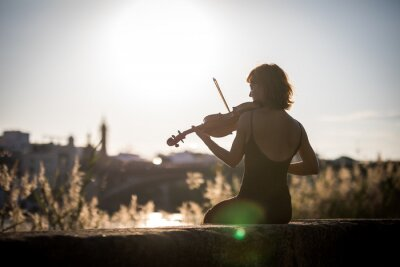 Plakat Young woman violinist posing playing on the street during sunset against light