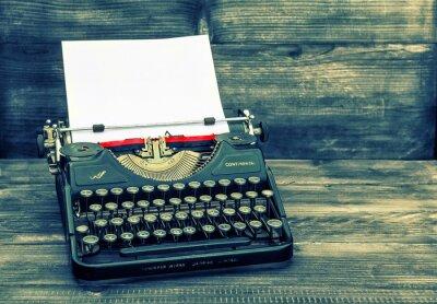 Plakat Zabytkowe maszyny do pisania z białym papierze stronie na drewnianym stole
