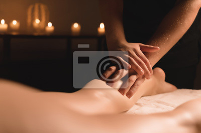 Plakat Zakończenie męskie ręki robi łydkowemu masażowi żeńskie nogi w ciemnym pokoju z świeczkami w tle. Zabiegi kosmetyczne i spa