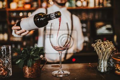 Plakat Zamyka w górę strzału barman nalewa czerwone wino w szkło. Koncepcja gościnności, napojów i wina.