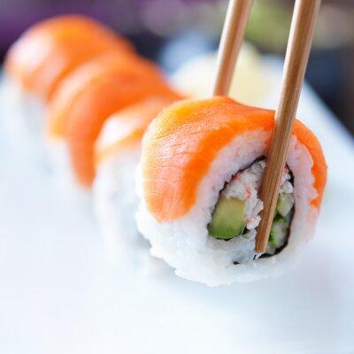 Plakat zbierając kawałek sushi pałeczkami
