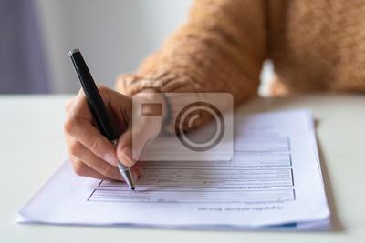 Plakat Zbliżenie formularza wypełnienia pani. Nie do poznania kobieta w swetrze siedzi przy stole i przygotowuje jej CV. Koncepcja poszukiwania pracy