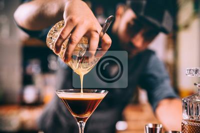 Plakat zbliżenie ręki barmana, wlewając koktajl alkoholowy w kieliszku martini