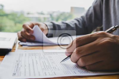 Plakat Zbliżenie ręki mężczyzna wypełnia podatek dochodowy formy